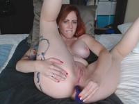 Redhead is sticking a dildo inside